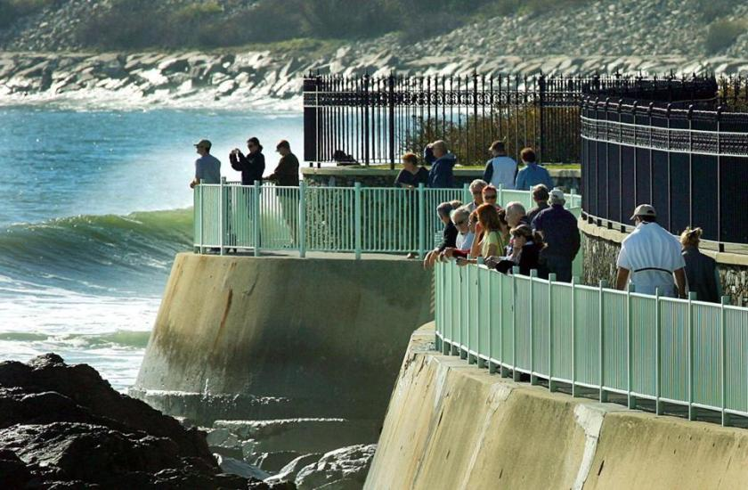 People along the Cliff Walk look to the heavy surf and hardy surfers on a fall day.